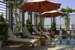 Sillas de playa por una piscina Fotografía de archivo