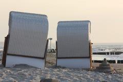 Sillas de playa y castillo de arena en la playa imagenes de archivo