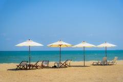 Sillas de playa y paraguas blanco en la playa tropical Foto de archivo