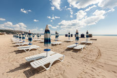 Sillas de playa y paraguas cerrados en la playa hermosa con el cielo azul nublado Foto de archivo