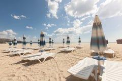 Sillas de playa y paraguas cerrados en la playa hermosa con el cielo azul nublado Foto de archivo libre de regalías
