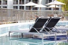 Sillas de playa y piscina lateral del paraguas fotos de archivo