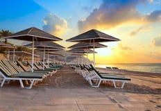 Sillas de playa y umrellas en el amanecer Imagen de archivo libre de regalías
