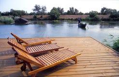 Sillas de salón en un muelle del lago Fotos de archivo libres de regalías