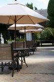 Sillas de tablas de los paraguas del moreno del café fotografía de archivo