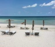 Sillas del paraguas y de cubierta de la choza en la playa arenosa cerca del SE azul imagenes de archivo