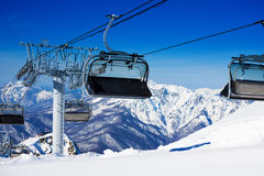 Sillas en el ferrocarril aéreo de la telesilla en montañas del invierno Imagen de archivo