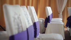 Sillas magníficas de la boda con las cubiertas del blanco y cinta púrpura para la ceremonia de boda almacen de metraje de vídeo