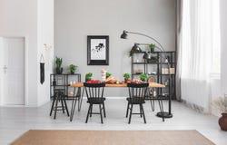 Sillas negras en la mesa de comedor con la comida en interior del apartamento con la lámpara y el cartel en la pared gris fotos de archivo