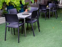 Sillas negras y tabla de mármol en hierba verde artificial imagen de archivo libre de regalías