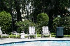 Sillas por la piscina fotos de archivo