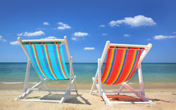 Sillas rayadas en la playa Fotografía de archivo libre de regalías