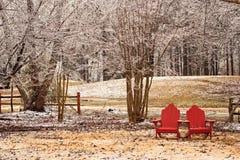 Sillas rojas de Adirondack en una tormenta de hielo Imágenes de archivo libres de regalías