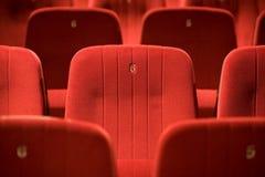 Sillas rojas en el cine vacío imagenes de archivo