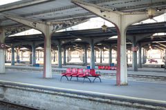 Sillas rojas en una estación de tren rumana con los pilares simétricos Fotografía de archivo