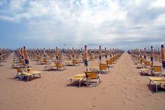 Sillas, sillas de playa y paraguas cerrados Fotos de archivo