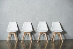 sillas vacías blancas para la entrevista de trabajo que se coloca en línea en pasillo imagenes de archivo