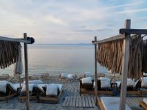 Sillas y camas blancas en costa cerca del mar azul hermoso foto de archivo