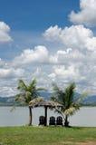 Sillas y choza por la orilla del lago imagen de archivo