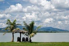 Sillas y choza por la orilla del lago fotos de archivo