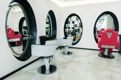 sillas y espejos de los peluqueros imagen de archivo