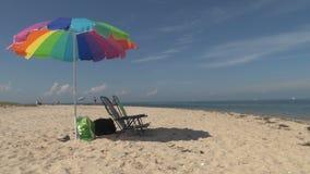 Sillas y paraguas coloridos de playa en la playa almacen de video