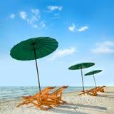 Sillas y paraguas de playa en la playa imagen de archivo