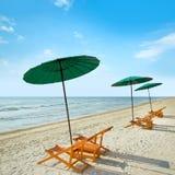 Sillas y paraguas de playa en la playa fotos de archivo