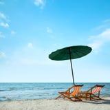 Sillas y paraguas de playa en la playa foto de archivo