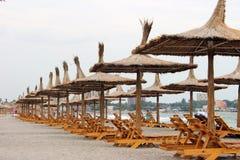 Sillas y paraguas en la playa foto de archivo