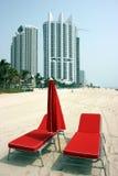 Sillas y paraguas rojos de playa Imagenes de archivo