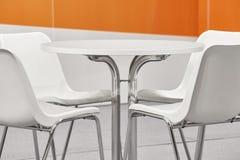 sillas y sistema plsticos blancos de la tabla decoracin anaranjada de la pared imagen de archivo
