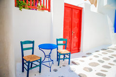 Sillas y tabla azules en la calle del pueblo tradicional griego típico con las casas blancas en la isla de Mykonos, Grecia, Europ Fotos de archivo
