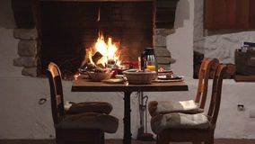 Sillas y tabla cerca de la chimenea, preparación deliciosa de la comida, espera para los pares de los amantes, cena romántica, co metrajes