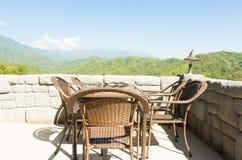 Sillas y tabla de la rota en terraza en montañas Foto de archivo