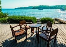 Sillas y tabla de madera en terraza abierta de la playa Fotografía de archivo libre de regalías