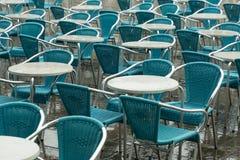 Sillas y tablas del café en la lluvia Foto de archivo