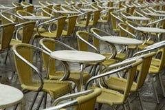 Sillas y tablas del café en la lluvia Foto de archivo libre de regalías