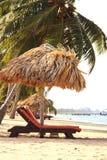Sillas y una choza del tiki en la playa imagenes de archivo
