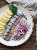 Sillfisk med potatisskivor och den röda löken Royaltyfri Foto