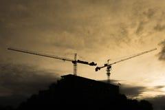 Sillhouette av byggnadskonstruktion med kran två Fotografering för Bildbyråer