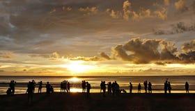 Sillhouette av en grupp av strandgoers som tycker om solnedgången över T Royaltyfri Foto