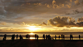 Sillhouette of a bunch of beach goers enjoying the sunset over T Royalty Free Stock Photo
