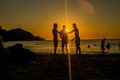 Sillhouette de trois démons appréciant dans la plage Images libres de droits