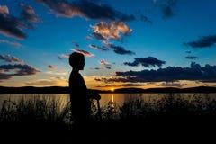 Sillhouette de um menino em um 'trotinette' durante o por do sol, olhando através de Hudson River, Tarrytown, do norte do estado  imagens de stock