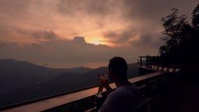 Sillhouette del giovane che beve cocktail in caffè con la vista di tramonto sull'isola tropicale video d archivio