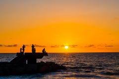 Sillhouette della gente nella spiaggia durante il tramonto Immagini Stock