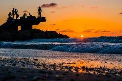 Sillhouette della gente nella spiaggia durante il tramonto Fotografie Stock Libere da Diritti