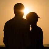 Sillhouette des couples affectueux au coucher du soleil Photo stock