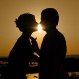 Sillhouette des couples de baiser au coucher du soleil Photos libres de droits